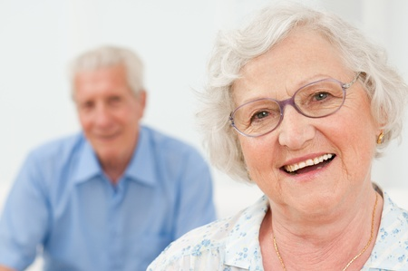 male senior adult: Happy senior woman smiling with her husband on background