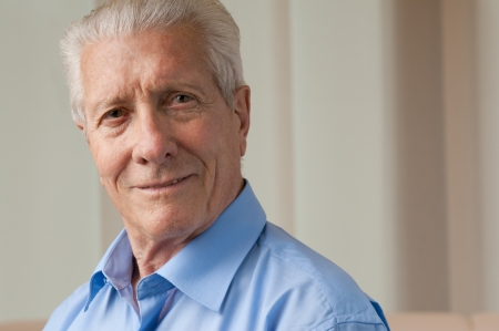 older people: Smiling satisfied senior man looking at camera at home, copy space Stock Photo