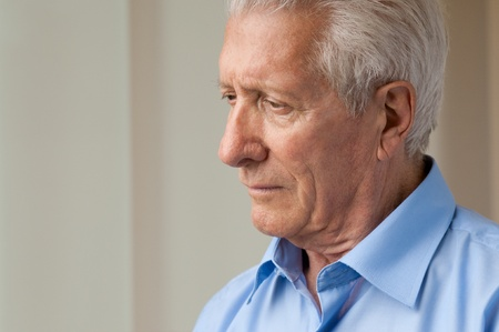 Sad senior man looking down with anxiety  photo