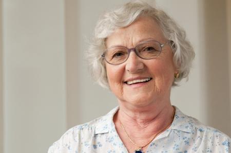 senior home: Happy smiling senior woman looking at camera at home