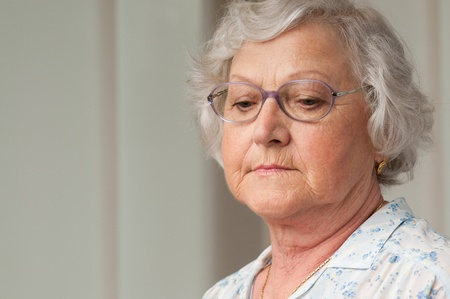 Senior aged woman looking down with sadness, indoor closeup shot photo