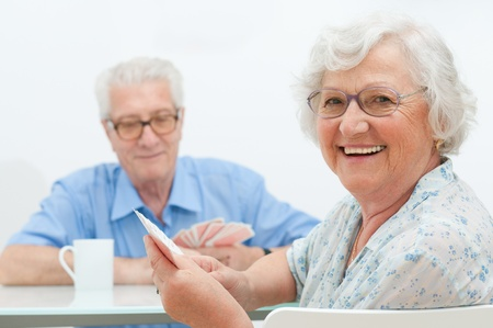 seniors homes: Happy smiling senior couple playing cards together at home Stock Photo