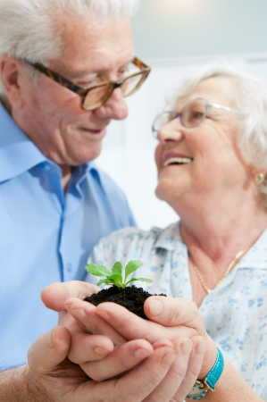 Old retired couple holding a fresh plant in their hands, symbol of good bank investments for the retirement photo