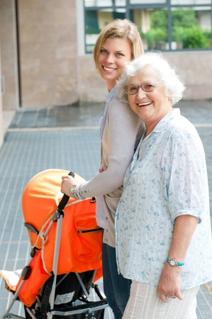 Happy smiling grandmother walking with her granddaughter and pushing a baby stroller, three generation family outdoor photo