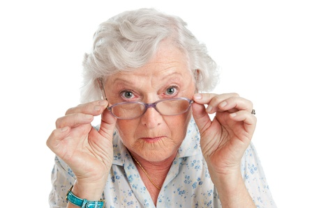 Happy surprised old senior lady looking through her eyeglasses isolated on white background photo