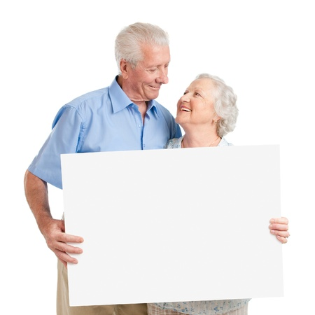 elderly couples: Senior lovely couple holding together a white board isolated on white background