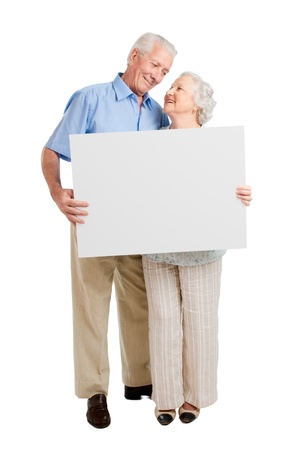 Happy full length senior couple standing together and holding a white board isolated on white background photo