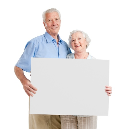 holding a sign: Smiling aged retired couple holding together a white board isolated on white background Stock Photo