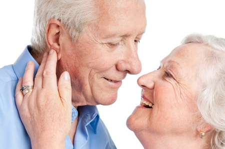 Sweet loving senior couple flirting together during the old age isolated on white background photo