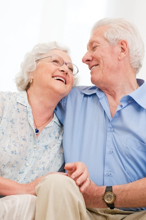couple laughing: Happy smiling senior couple laughing together at home