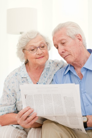 Happy relaxing senior couple reading newspaper together at home photo