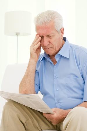 hombre preocupado: Senior hombre tiene problemas con la vista al leer un peri�dico en casa Foto de archivo