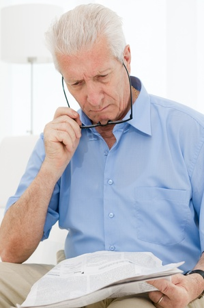 Senior man having trouble with eyesight while reading a newspaper at home