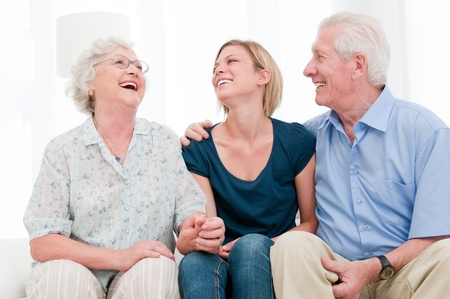 Happy smiling girl staying together with her grandparents at home photo