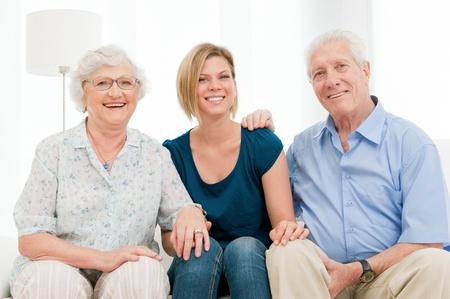 abuela: Smiilng familiy feliz con nieta y abuelos mirar juntos en la cámara en casa Foto de archivo