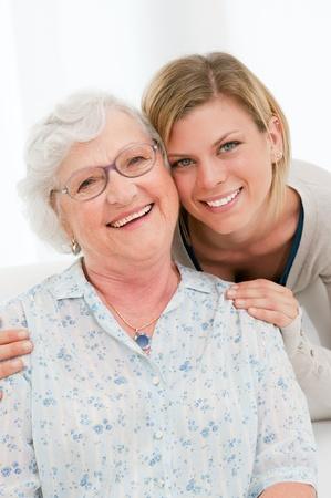 abuela: Sonriendo granddaugther abrazo de su abuela en casa