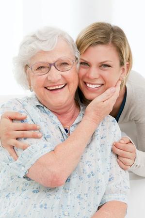 abuela: Feliz mujer mayor afectuoso abrazo a su nieta en su casa Foto de archivo