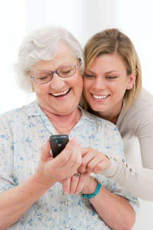 telephone together: Young smiling granddaughter showing and teaching a mobile phone to her grandmother  Stock Photo