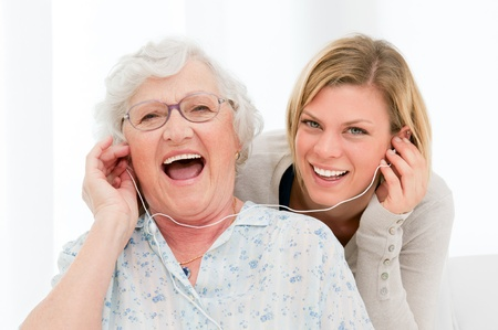 grandparent: Super happy and excited grandmother listening music with her granddaughter at home Stock Photo