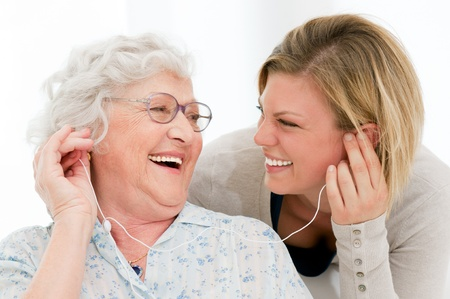 Excited grandmother listening music together with her granddaughter at home photo