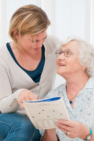 Senior lady solving crosswords puzzle with the help of her young granddaughter at home photo