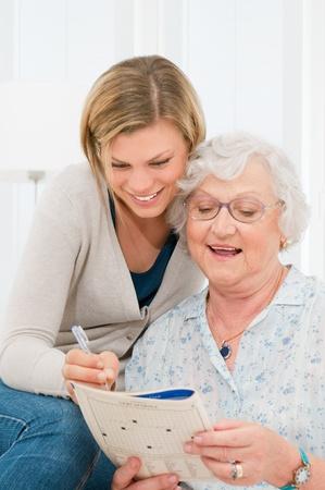 personas ayudando: Se�ora tercera edad activa la soluci�n de rompecabezas crucigramas con la ayuda de su nieta Foto de archivo