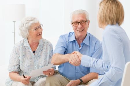 anciano feliz: Feliz pareja senior sellado con un apret�n de manos de un contrato para la jubilaci�n