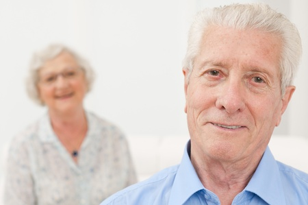 Smiling senior man smiling with his old wife in background photo