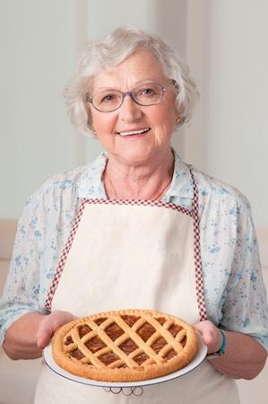 abuela: Feliz sonriente mujer mayor que muestra su tarta de albaricoque Foto de archivo