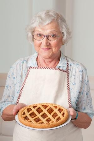 grandmas: Feliz sonriente mujer mayor que muestra su tarta de albaricoque Foto de archivo