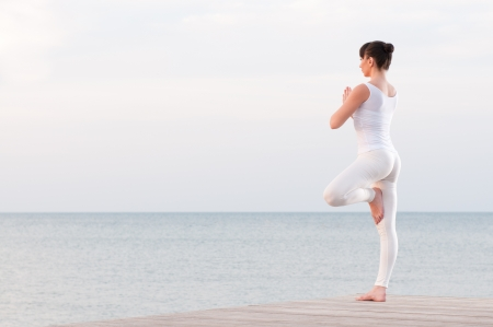 Young healthy woman standing on one leg while meditating and praying outdoor at sea photo