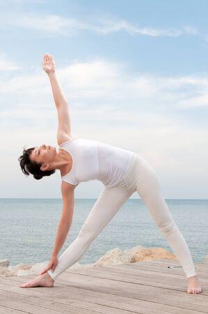 trikonasana: Healthy young woman practise yoga outdoor at sea: trikonasana pose Stock Photo