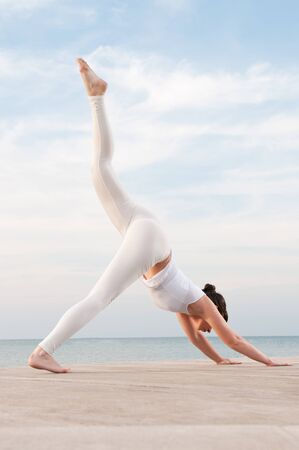 Young beautiful woman doing yoga exercise outdoor at sea: Parvatasana pose photo