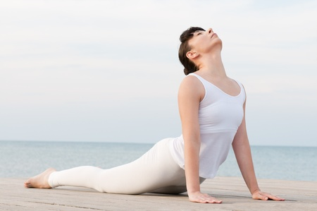 Young healthy woman doing yoga position at sea: Cobra pose photo