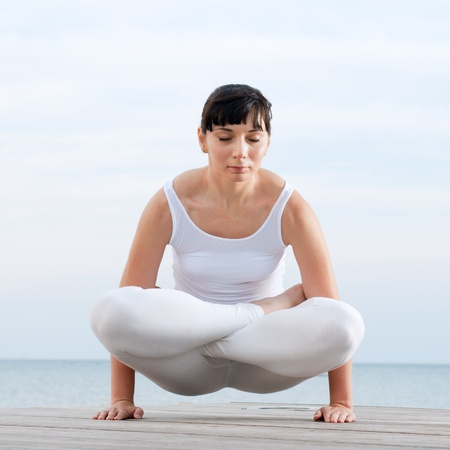 Young woman doing yoga position outdoor at sea Stock Photo
