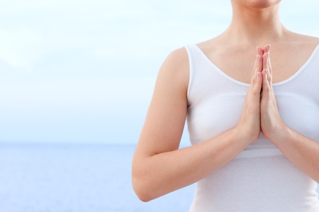 female pose: Close up of hands in praying and yoga pose outdoor at sea