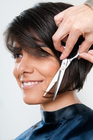 sal�n: Hermosa mujer joven feliz cortando el pelo en la peluquer�a