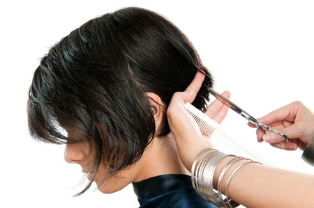 cutting hair: Young lady cutting hair at the hairdresser isolated on white background