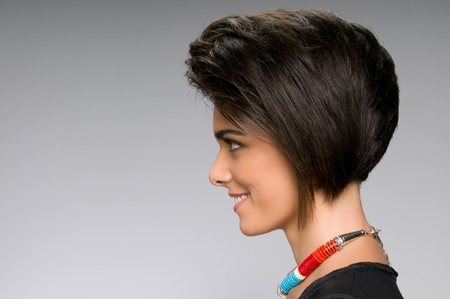 Profile of beautiful young woman with straight short hairstyle on gray background photo