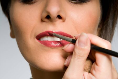 Young woman applying red lipstick with a makeup brush photo