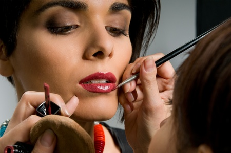 Professional makeup artist applying red lipstik on a fashion model lips before the stage photo