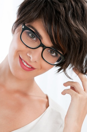 Beautiful smiling young woman with trendy eyeglasses and hairstyle isolated on white background photo