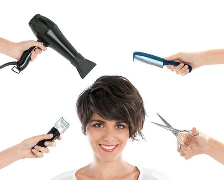 peluquerias: Feliz mujer joven y sonriente con las herramientas de peluquer�a entre sus aisladas sobre fondo blanco Foto de archivo