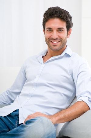 beau jeune homme: Heureux jeune homme souriant se détendre sur le canapé à la maison