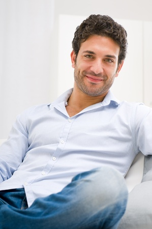Smiling young man relaxing and sitting on sofa at home photo