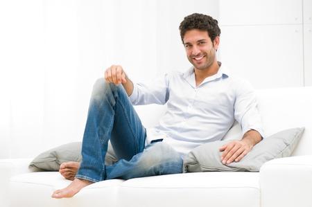 Happy lachende man te ontspannen en zittend op de sofa thuis