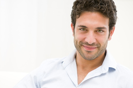 Close up of satisfied smiling guy looking at camera at home photo