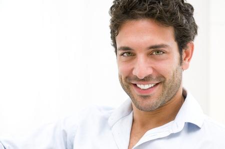beau jeune homme: Gros plan d'un jeune homme heureux en regardant la caméra à la maison