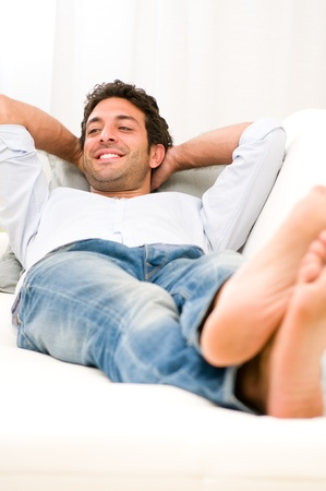 Young man relaxing and taking a break on sofa at home Stock Photo - 11742917
