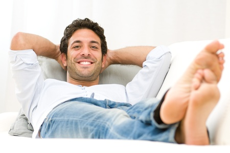 Smiling healthy young man relaxing on sofa and looking at camera Stock Photo - 11742927